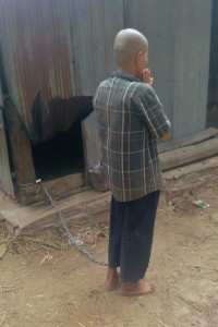 Person with mental illness chained to the wooden pillar of a rural house.